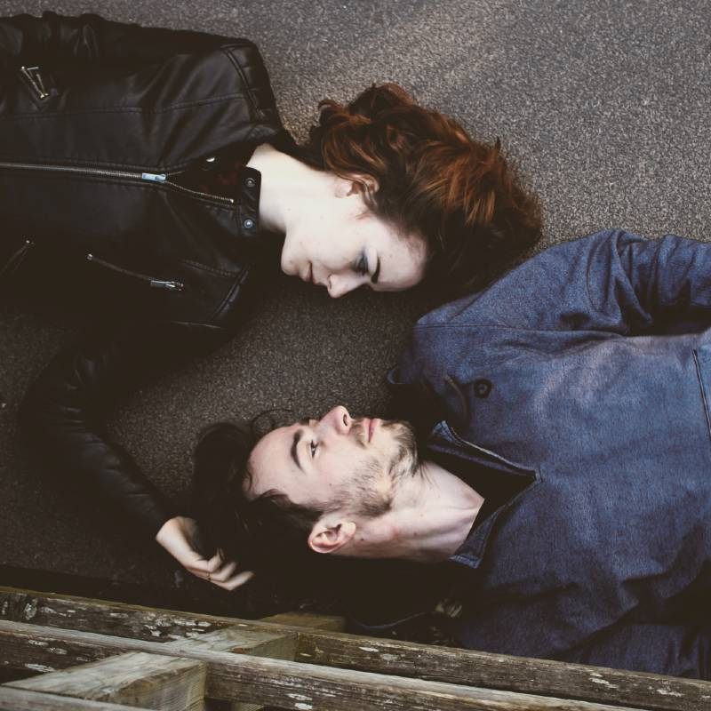 Man and Woman Lying on Ground